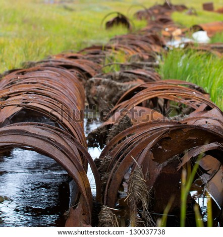 the pipeline among North permafrost from old barrels - stock photo