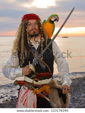 The pirate with a parrot on the seashore - stock photo