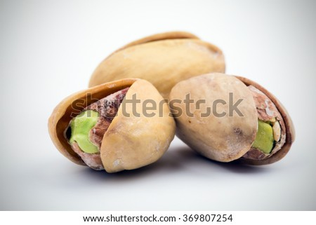 The pistachios heap against the background of wooden boards - stock photo