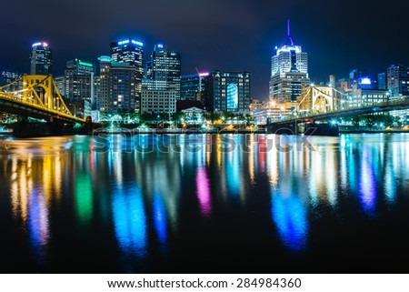 The Pittsburgh skyline reflecting in the Allegheny River at night, seen from the North Shore, in Pittsburgh, Pennsylvania. - stock photo