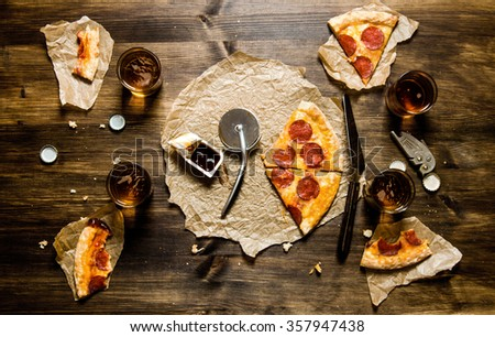 The pizza party. Pepperoni pizza and beer for four people. On a wooden table. Top view - stock photo