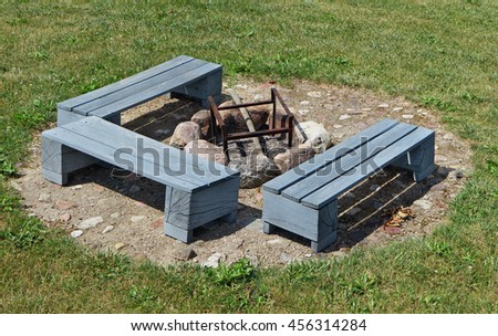 The place for a barbecue on a green grass of a garden lawn. Wooden handmade  benches are painted with gray paint. The brazier is made of granite stones