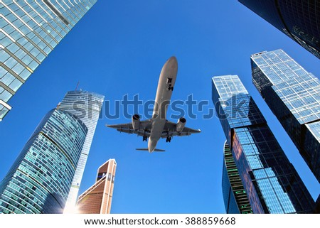 The plane is flying very low over the skyscrapers - stock photo