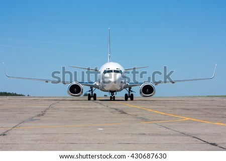 The plane moves on the taxiway in the hot summer day