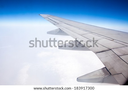 The plane's wings, the background is blue sky, taken from the cabin