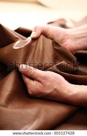 The plant leather craftsman. Hands tailor to check the quality of the material  - stock photo