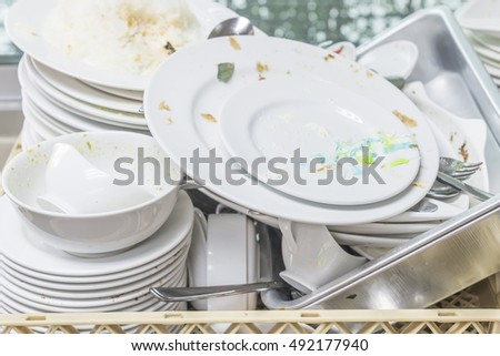 The plate dishes in the kitchen waiting for cleaners in sink
