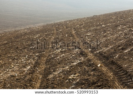 The ploughed field with wheel tracks before sowing.