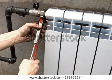 the plumber makes installation a heater radiator - stock photo