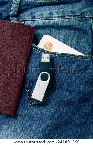 The pocket of jeans with document, money amd flash card. Cloth background. Toned. - stock photo