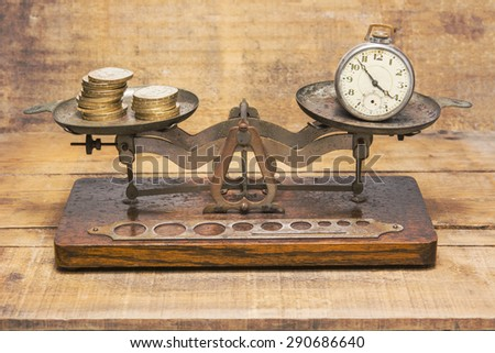 The pocket watch and golden coins on the balance scale - stock photo