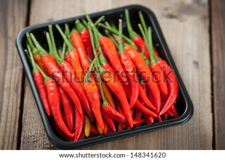 The pods of red chili peppers on a wooden background - stock photo