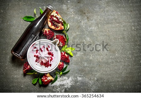The pomegranate juice in a bottle with the juice and slices of ripe pomegranate. On the stone table. Free space for text . Top view - stock photo