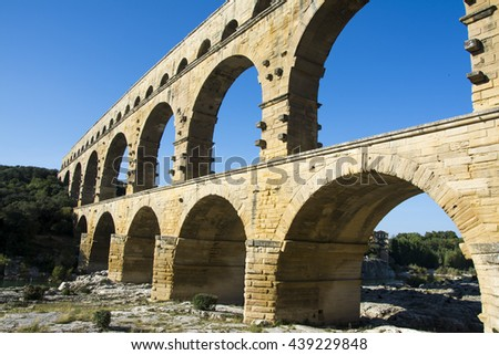 The Pont du Gard is an ancient Roman aqueduct that crosses the Gardon River in southern France. - stock photo