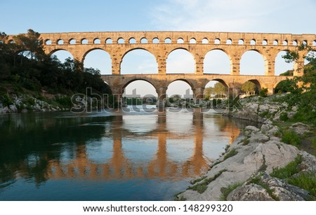 The popular among tourists roman bridge Pont du Gard looks to a mirror on the Gardon river, located near Avignon, France..