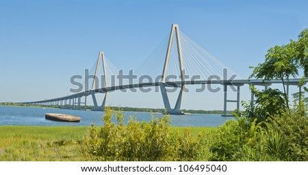 The Port of Charleston, a cable stayed bridge, an abandoned barge, and the Cooper River in Charleston, South Carolina.