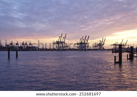 The Port of Hamburg with some container gantry cranes as silhouettes against the sky taken in the evening at the point of the blue hour.
