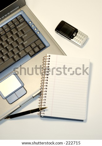 The portable office. Laptop, notepad, pen, cell phone. - stock photo