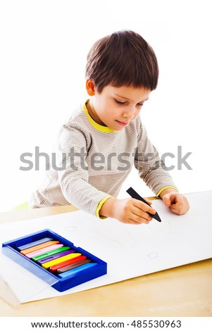 The portrait of a little boy drawing using colored pencils.