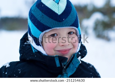 The portrait of happy caucasian boy in snowing winter outdoor - stock photo