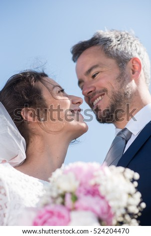 the portrait of newlywed with a bouquet. shooting from below. the young couple is smiling. the bride wear a veil and a white dress.