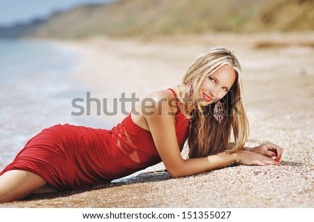 the portrait of the beautiful fashionable woman in an evening dress lies at the sea in waves