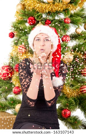 The portrait of the woman blowing kiss on the christmas tree background.