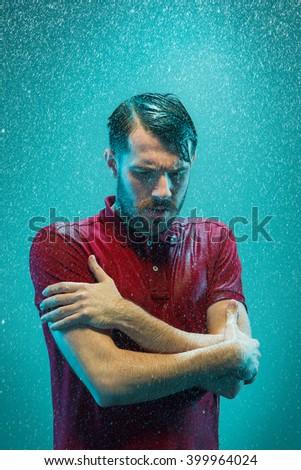 The portrait of young man in the rain - stock photo