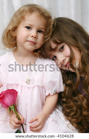 The Portrait two girls teenager with red rose on light background. - stock photo