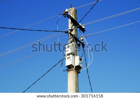 The post power lines with power line cables and electricity meters against the blue sky - stock photo