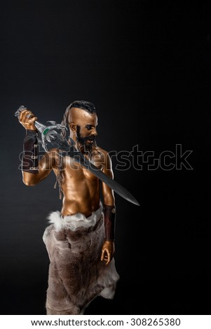 The powerful Gold soldier with sword on black background. - stock photo