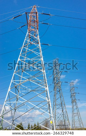 The powerlines on the large green field - stock photo