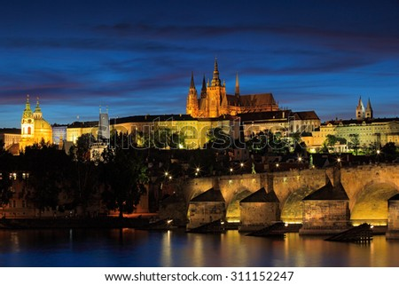 The Prague Castle, gothic style,  largest ancient castle in the world, and Charles Bridge are the symbols of Czech capital, built in medieval times. Twilight view of Prague, after sunset
