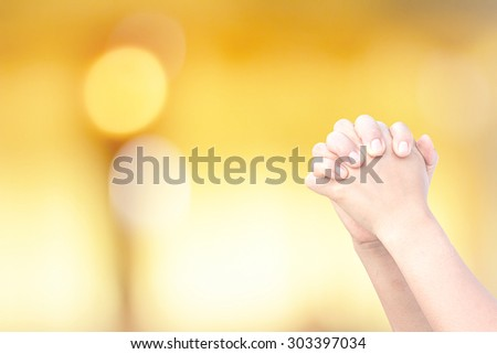 The praying hands on the background bokeh blur. - stock photo