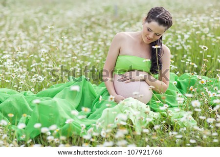 The pregnant woman among a field of flowers