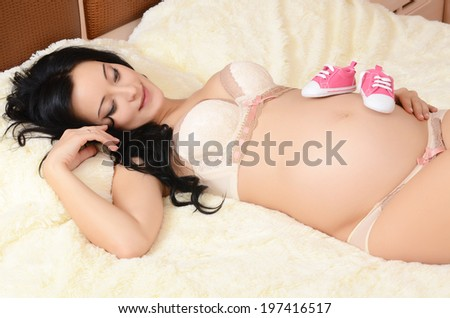 The pregnant woman on bed in room
