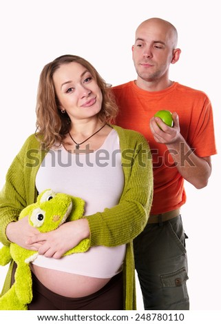 the pregnant woman with her husband with green apple on the white background