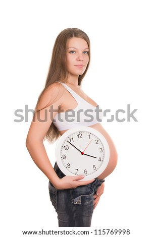 The pregnant young woman holds white clocks - stock photo