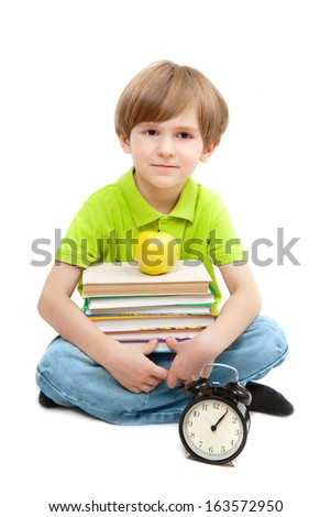 The preschooler with a pile of books, apple and alarm clock - stock photo
