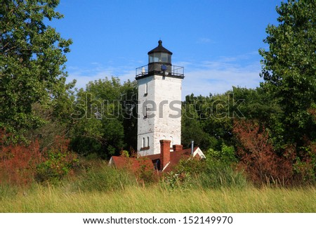 The Presque Isle Lighthouse Tower Rising Above A Sand Dune Covered In Beach Grass On A Warm Summer Afternoon Along Lake Erie At Erie Pennsylvania, USA - stock photo