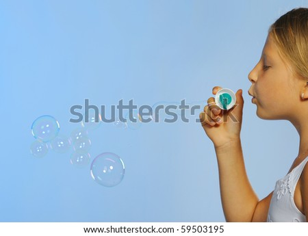 The pretty girl with soap bubbles. A  blue background - stock photo