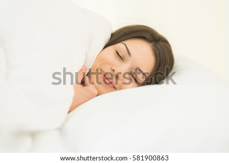 The pretty woman sleeping in the white linens