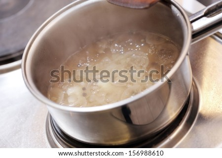 The process of a sauce being prepared in a pan - stock photo