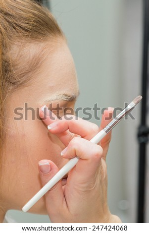 The process of applying makeup to the face model. Powder, eye shadow, brush for applying makeup. Make up artist with professional model working with professional model. - stock photo