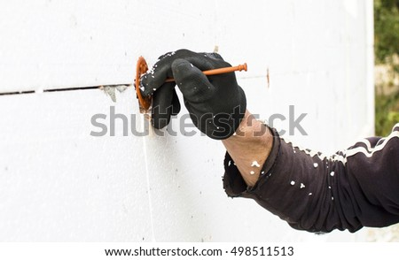 The process of fixing dowel-umbrella on the walls with foam plastic