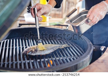 the process of making fresh raw fish dorado hands chef puts fish on the grill roaster - stock photo