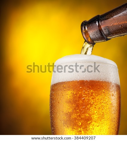 The process of pouring beer into the glass. Bright orange background.