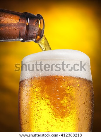 The process of pouring beer into the glass. Bright orange background. - stock photo