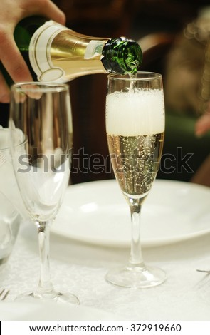 the process of pouring champagne into a glass