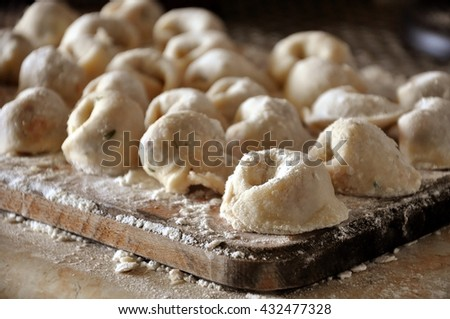 The process of preparation of Russian meat dumplings. Homemade raw dumplings with flour on a wooden board. Close up.